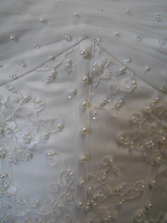 bodice is adorned with applique and faux pearls