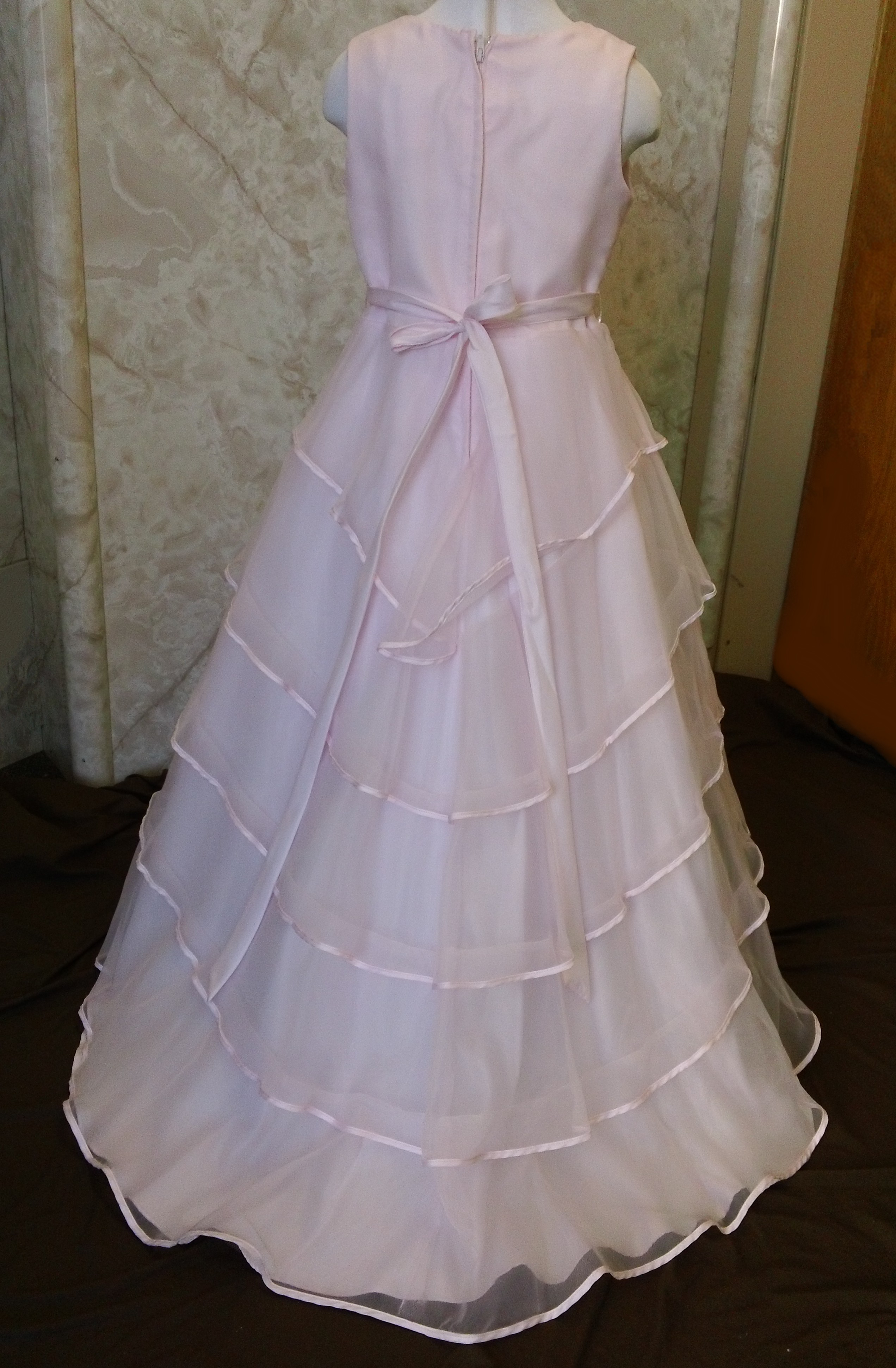 Long sleeveless girls pink dress with 5 tier skirt.  Zipper back, with tie sash.