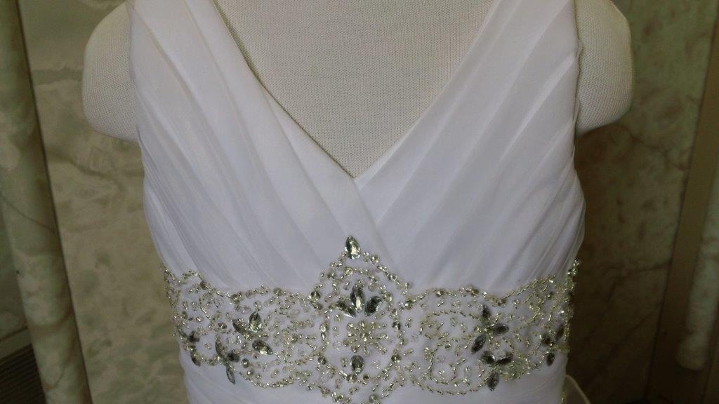 ruched bodice is edged with a jeweled belt