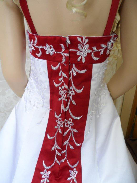 white embroidered on red train of miniature wedding gown