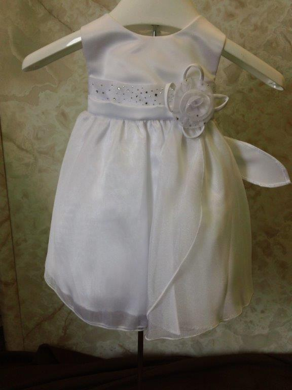 white infant dress with sequins and ribbon flower