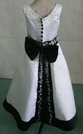 White sleeveless dress with black trim and rich embroidery