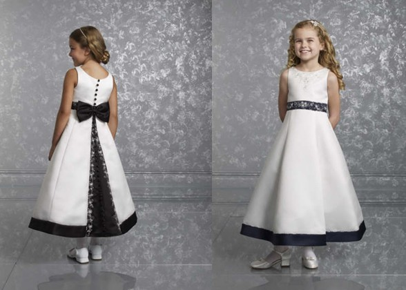 White Sleeveless Flower Girl Dress. Black contrasting covered buttons, bow and trim
