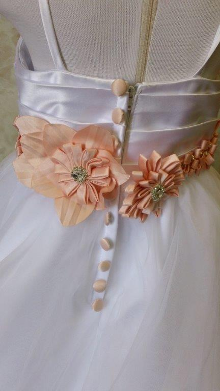 white flower girl dress with sherbert flowers