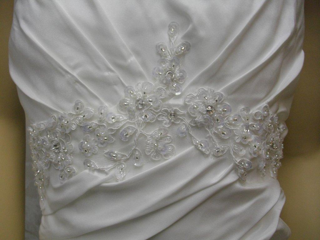 lace applique enriches the pleated empire bodice