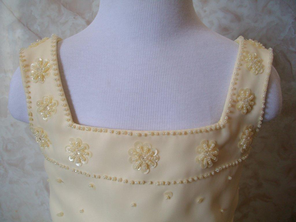 Flowers made out of beading and sequins adorn the square neckline of this buttercup yellow dress