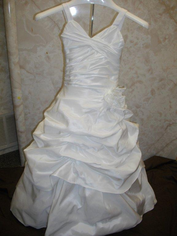 bridal gown has wide straps with a draped pick-up layer over an A-line skirt